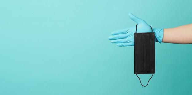 Uma mão em luvas médicas ou luvas de látex segurando a máscara preta isolada em fundo azul e verde ou azul tiffany.