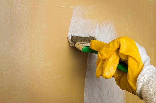 Uma mão em uma luva amarela pinta a parede de branco com um pincel.