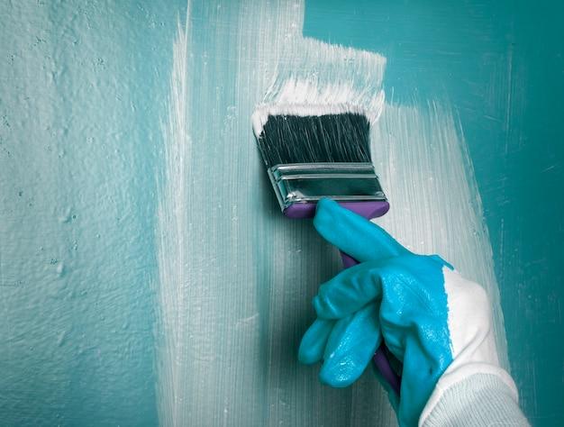 Uma mão em uma luva azul desenha com um pincel em uma parede azul.