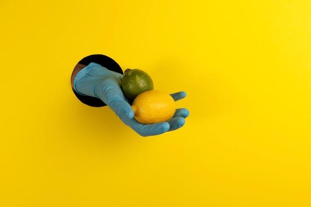 Uma mão em uma luva azul em um buraco em um fundo amarelo e oferece limão e lima
