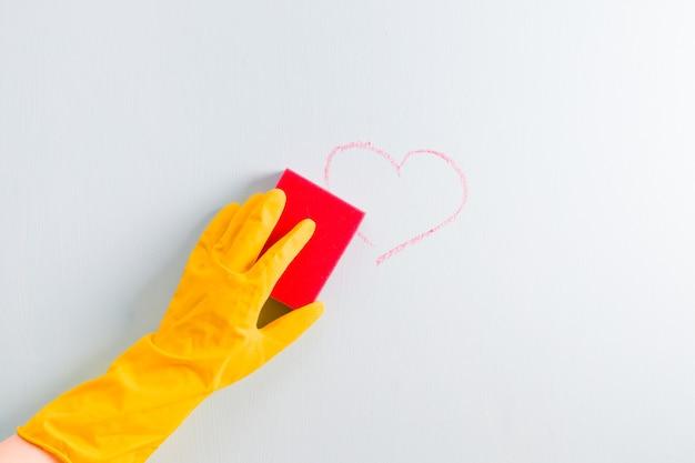 Uma mão em uma luva de borracha amarela limpa um coração marcado com giz na parede com uma esponja