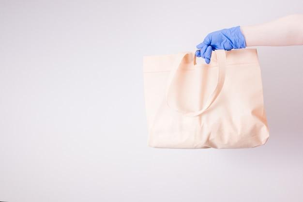 Uma mão em uma luva de borracha azul segura uma sacola de compras, fundo claro, espaço de cópia, conceito de entrega sem contato