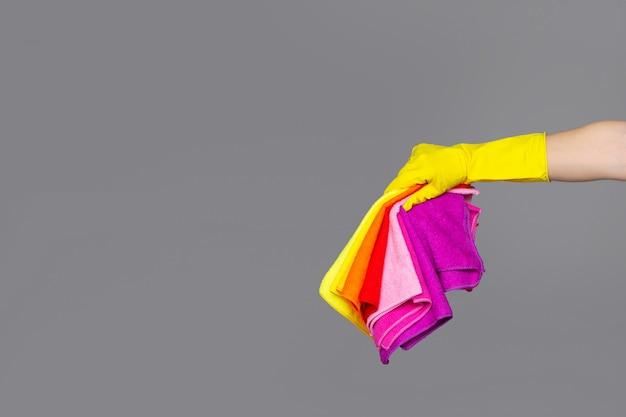 Uma mão em uma luva de borracha contém um conjunto de panos de microfibra coloridos em cinza
