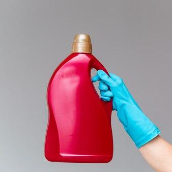 Uma mão em uma luva de borracha contém uma garrafa de detergente de canalização