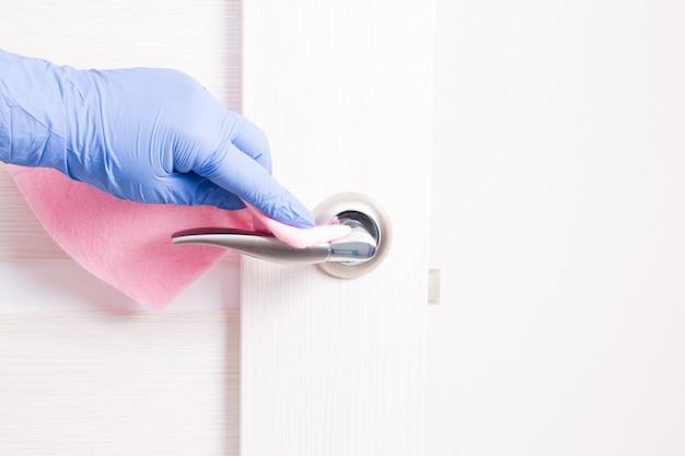 Uma mão em uma luva de borracha descartável azul limpa uma maçaneta com um pano rosa, limpando e desinfetando superfícies