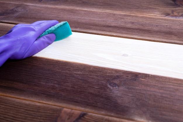 Uma mão em uma luva de borracha lava uma superfície de madeira. limpeza, limpeza do quarto.