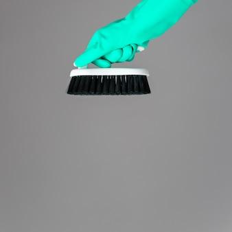 Uma mão em uma luva de borracha mantém a escova de lavar louça em neutro