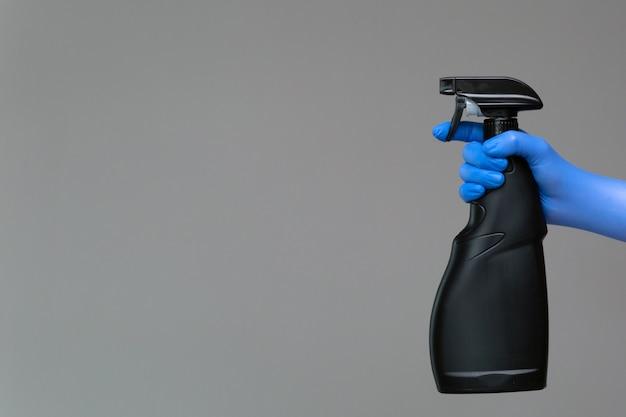 Uma mão em uma luva de borracha mantém o limpador de vidro em um frasco de spray em um fundo neutro.