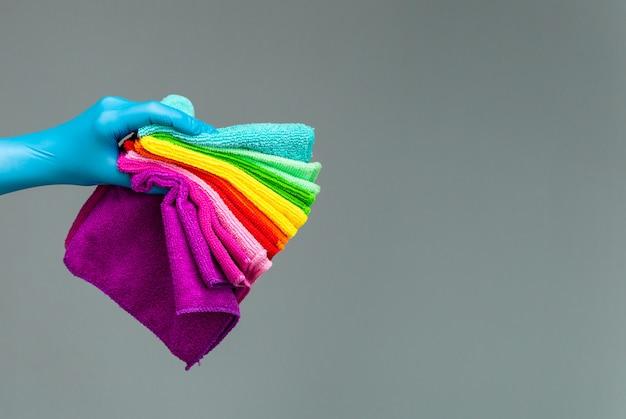 Uma mão em uma luva de borracha mantém um conjunto de panos de microfibra colorido sobre um fundo neutro.