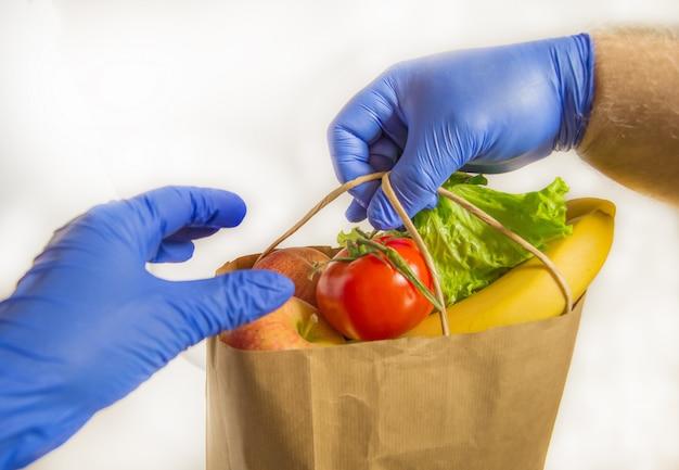 Uma mão em uma luva de borracha passa por uma sacola de legumes e frutas, entrega de correio seguro, entrega sem contato, assistência voluntária em caso de pandemia