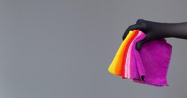 Uma mão em uma luva de borracha possui um conjunto de microfibra colorido