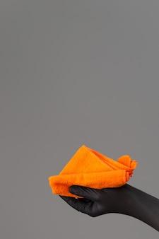Uma mão em uma luva de borracha possui um espanador micro fibra brilhante