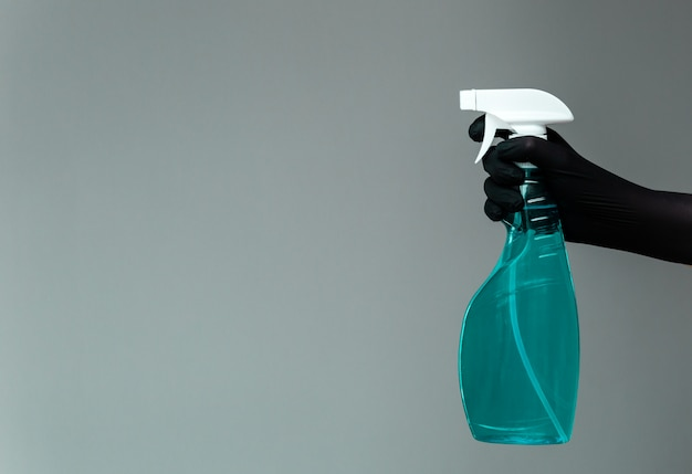 Uma mão em uma luva de borracha segura o limpador de vidro em um frasco de spray em um neutro.