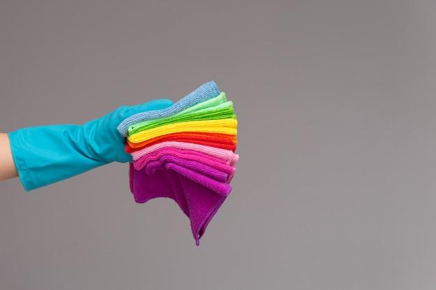 Uma mão em uma luva de borracha segura um conjunto de panos coloridos de microfibra sobre uma superfície neutra.