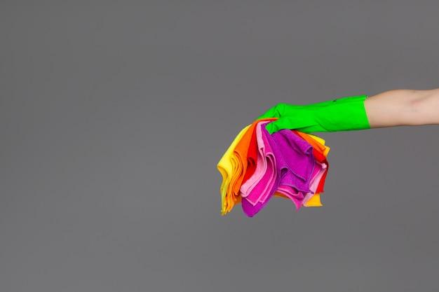 Uma mão em uma luva de borracha segura um conjunto de panos de microfibra coloridos em ponto morto.