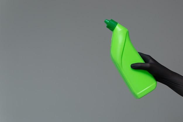Uma mão em uma luva de borracha segura uma garrafa de detergente de encanamento em uma superfície neutra.