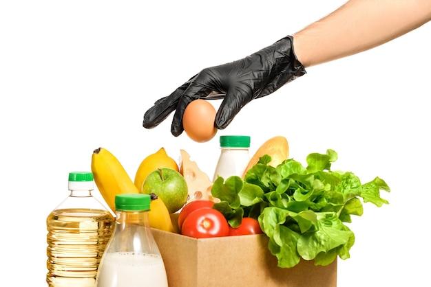 Uma mão em uma luva de proteção preta coloca um ovo em uma caixa de papelão com comida. entrega de comida segura. caixa de comida