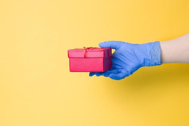 Uma mão em uma luva descartável azul segura uma caixa de presente vermelha com um laço de uma fita vermelha com fio dourado na superfície amarela