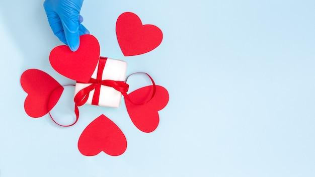 Uma mão em uma luva protetora azul segura um coração de papel vermelho sobre uma caixa de presente com uma fita vermelha