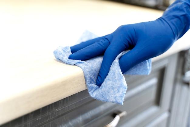 Uma mão enluvada limpa o pó da bancada.