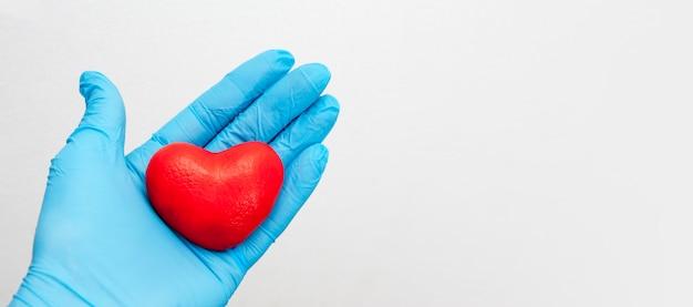 Uma mão enluvada segura um coração vermelho. conceito de assistência médica. copie o espaço