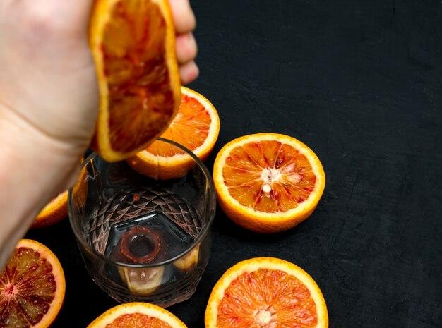 Uma mão espreme suco de metade da laranja vermelha em um copo de vidro. suco fresco.