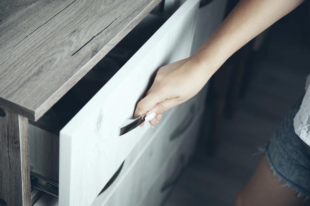 Uma mão está abrindo uma gaveta de madeira