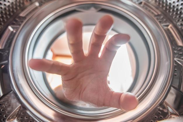 Uma mão está chegando a roupa dentro da máquina de lavar roupa.