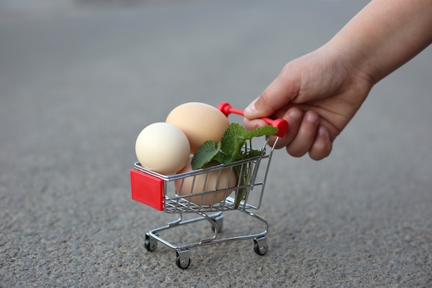 Uma mão está rolando um mini carrinho do supermercado com ovos.