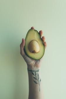 Uma mão fêmea com uma tatuagem ramo-dado forma prende uma metade de um abacate cru em um fundo liso.