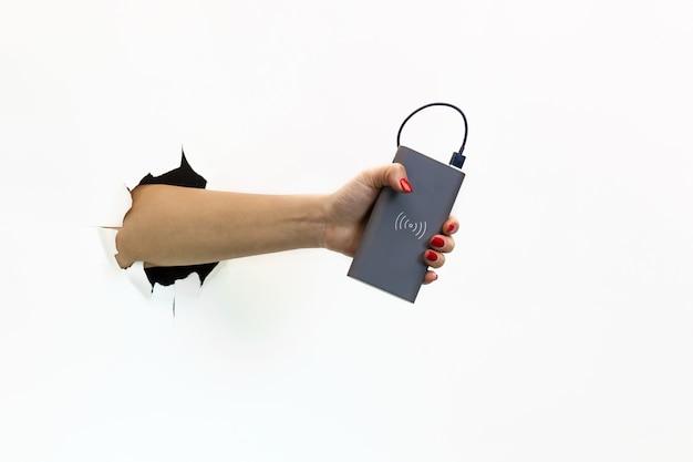 Uma mão feminina com uma manicure vermelha em um papel branco rasgado segurando um banco de energia