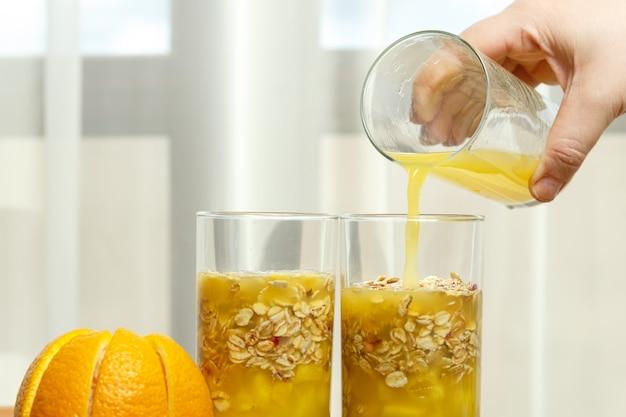 Uma mão feminina derrama suco de laranja em copos com pedaços de frutas.