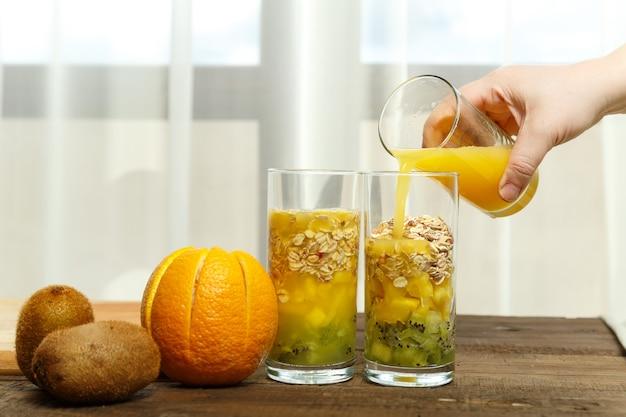 Uma mão feminina derrama suco de laranja em um copo com pedaços de frutas.