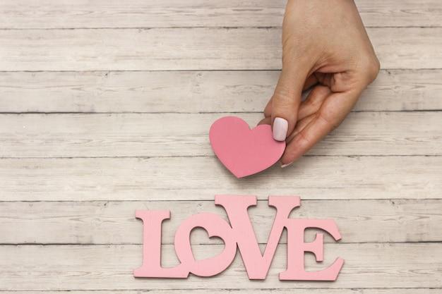 Uma mão feminina detém um coração de madeira, o conceito de amor
