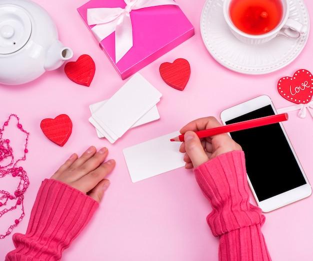 Uma mão feminina detém um lápis de madeira vermelho e assina cartões de visita de papel branco