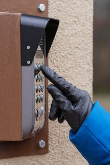 Uma mão feminina disca o código no interfone. fechar-se.