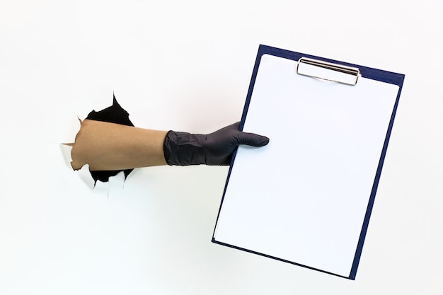 Uma mão feminina em uma luva de látex preta através de um papel rasgado em um fundo branco segura um tablet para papel a4. quarentena medidas para evitar a propagação de covid 19. mão enluvada através de papel rasgado.