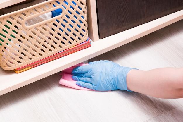 Uma mão feminina em uma luva descartável de borracha com um pano rosa limpa a poeira debaixo do armário