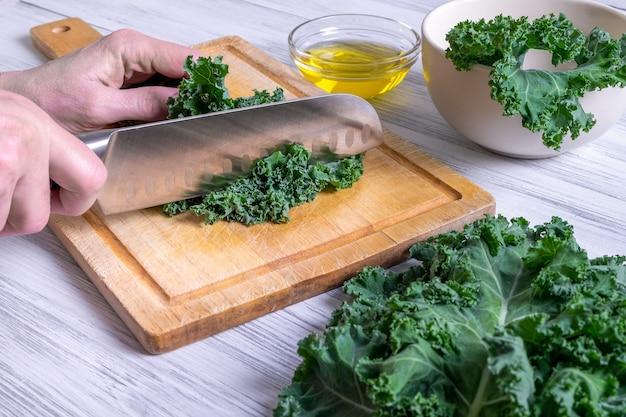 Uma mão feminina está cortando as folhas de couve com uma grande faca de cozinha em uma tábua de madeira