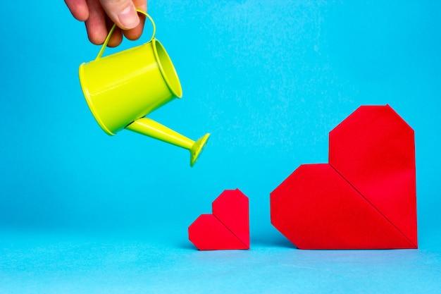 Uma mão feminina rega dois corações vermelhos sobre um fundo azul.