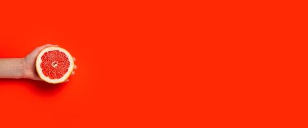 Uma mão feminina segura metade de uma toranja em um fundo vermelho. vista superior, configuração plana.