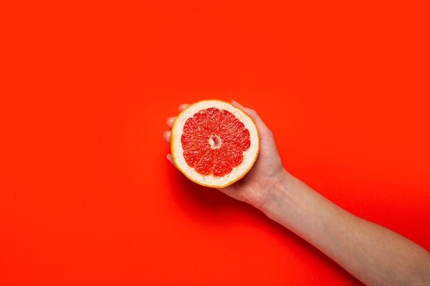 Uma mão feminina segura metade de uma toranja em uma superfície vermelha. vista superior, configuração plana. bandeira.