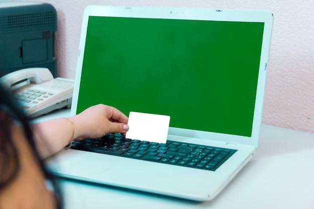 Uma mão feminina segura um cartão do banco ao pagar compras online na tela verde. foto horizontal