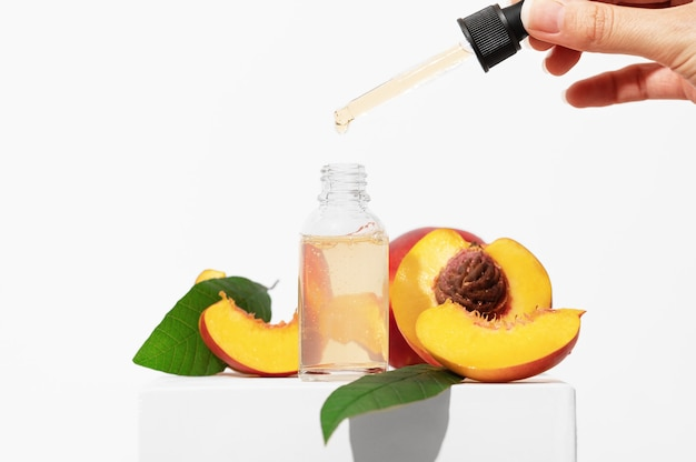 Uma mão feminina segura um conta-gotas com um soro cosmético. produto cosmético natural para a pureza e hidratação da pele. frasco de vidro com um produto para o rosto feminino em um suporte branco com frutas pêssego.