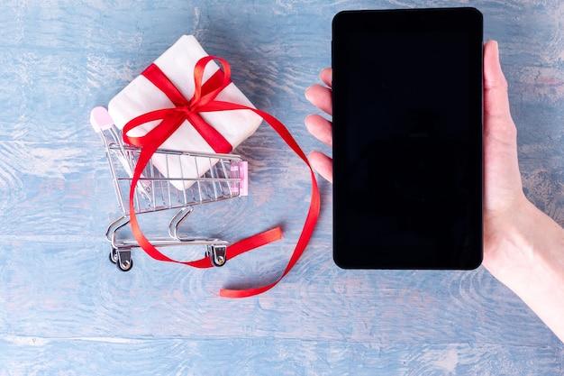 Uma mão feminina segura um telefone celular com uma tela preta em branco para compras online e um carrinho de compras com uma caixa de presente em um fundo azul de madeira. conceito de compras online