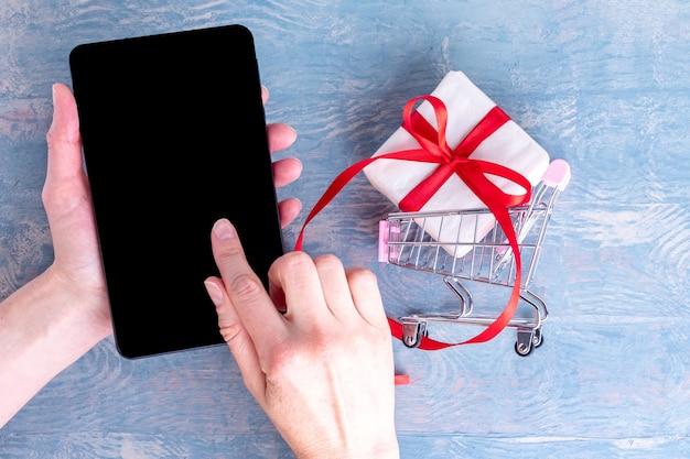 Uma mão feminina segura um telefone celular e um dedo pressiona uma tela preta em branco para comprar produtos na internet e um carrinho de compras com uma caixa de presente em um fundo azul de madeira