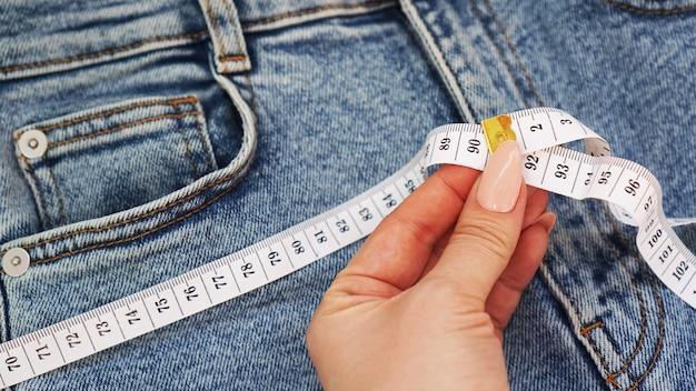 Uma mão feminina segura uma fita métrica em um fundo de jeans. conceito de jeans ou perda de peso