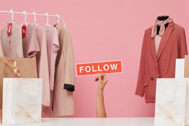 Uma mão feminina segurando um cartaz e dizendo para seguir sua loja de roupas