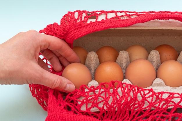 Uma mão feminina tira ovos crus naturais de uma caixa de papelão e de um saco de barbante vermelho. comprando o conceito de ovos. conceito de comida saudável