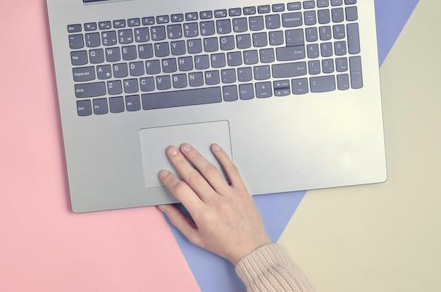 Uma mão feminina usa um laptop. uma tendência minimalista. trabalho online, freelancer, blog. vista superior em um pastel.